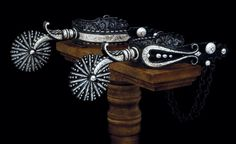 The buckaroo-style spurs are made of highly polished, blued steel, inlaid and overlaid with sterling silver.