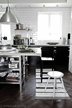 dark modern cabinets, stainless worktable, subway tile