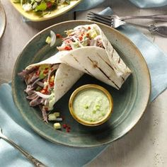 Shredded Pork Burritos Recipe -Pork roast is slow-cooked with savory and sweet ingredients, including a can of cola, to create tender, shredded pork burritos. A tomatillo sauce, made easy with a dressing mix, tops the pork for an out-of-this-world entree.—Katherine Nelson, Centerville, Utah