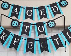 Handmade cardstock 50th Birthday Party banner with dimensional effects, ribbon embellishments, and metallic silver lettering. This Black, Turquoise, and Silver 50th Birthday Banner reads Aged to Perfection and makes an elegant addition to your 50th or 60th birthday party. Other wording, colors, and age is available, please message me for more information. Most customization requests can be accommodated. Please allow at least 7 days advanced notice for custom orders.