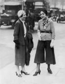 Innovative, witty Paris fashion designer Elsa Schiaparelli, right, in Hyde Park, London, wearing her 'trousered skirt' and illustrating her current fashion message: 'Trousers For Women!'