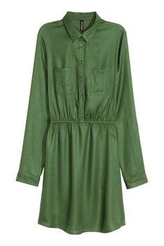 Szmizjerka: Krótka sukienka z wiskozowej tkaniny z koszulowym kołnierzykiem i z guzikami u góry. Kieszenie na piersi, elastyczne odcięcie w talii, długie rękawy z patką i guzikiem.