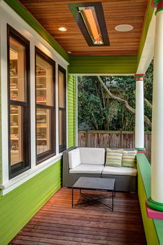 The cozy front porch has a built-in ceiling heater for comfortable socializing on cool evenings. Lime-green walls create a fun vibe in the small space. Kelly green and hot-pink caps on the white columns add an extra touch of color. A white-cushioned loveseat fits snugly on the far end of the porch.