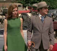 'The Fear Merchants', Series 5 ~ John Steed wears a single-breasted pale grey suit with notch collar, the upper portion is covered in velvet. The jacket has no breast pocket, and two slanted slit waist pockets; the skirt has two short vents. Worn with a white shirt (or maybe very pale pink), purple  blue patterned tie.  Emma wears a gray green sleeveless dress with pale tan stockings  tan shoes.