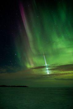 Meteor streaking through the Aurora Borealis