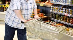 Obese shoppers: Subtle cues help shoppers skip unhealty choices: An obese man walks past healthy food in a supermarket