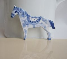 This brooch of a horse is hand formed of white porcelain that I decorated in the traditional Delft technique with cobalt oxide.  I covered it on one side with a strong transparent glaze and fired at it 2300 degrees F. or 1260 degrees Celsius. It measures about 2,6 x 2 inches or 7 x 5 cm.    Comes in a cute gift box with numbered product card.