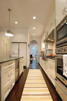 Traditional Kitchen with Flat panel cabinets, Galley, Undermount Sink, Hardwood floors, Simple granite counters, High ceiling