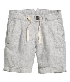 Light gray melange. Shorts in a linen and cotton blend. Adjustable elasticized waistband with ties at front and zip fly with button. Side pockets and welt