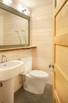 Weiße Toilette und Standwaschbecken-Holzverkleidete Wände-Mini-Bad vergrößert mittels Spiegel