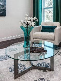 A bold, contemporary rug ties together the solid black-and-white pieces of this contemporary living room. A round, glass coffee table and bright turquoise curtains are modern additions to the space.