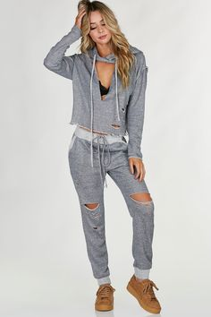 Long sleeve oversized hoodie with distressing throughout and cut out in front. Raw hem all around with reversed drawstrings for added detail. Comes in a set with matching bottoms sold separately.