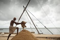 A worker in Lamu piles sand on a boat dock in Kenya - National Geographic