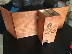 Wooden DM Screen and Dice Tower. the dice tower has one chute that shoots out the players' side and one that shoots into the private DM side.
