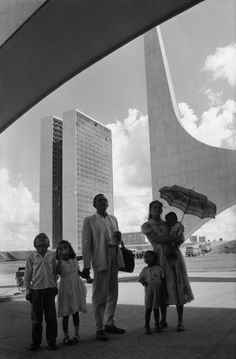 Worker from Nordeste shows his family the new city on inauguration day. In the background: the National Congress building by Oscar Niemeyer. Brasilia, Brazil. 1960. © Rene Burri | Magnum Photos