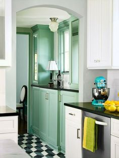 An arched opening invites the eye toward a handsome butler's pantry with cool-green beveled-mirror cabinet fronts. | Photo: Deborah Whitlaw Llewellyn | thisoldhouse.com
