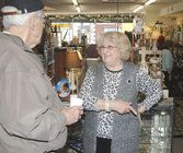 Mariam Cameron, owner of Mariam's Memories at 10 S.W. Third St., chats with Raymore resident Bill Welborn, who stopped Wednesday to shop and swap stories.