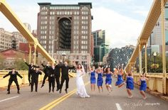 This wedding party jumps for joy on the 6th Street/Roberto Clemente Bridge in Pittsburgh. The groomsmen wear black suits and ties, with the bridesmaids in short royal blue dresses. In the center, the bride wears a stunning taffeta dress with a crystal belt and sweetheart neckline. A veil flows over her hair. The couple's wedding and reception were held in the nearby Fairmont Hotel, where The John Parker Band kept the party going all night long. http://www.jpband.com/weddings.html
