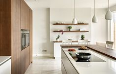 Modern walnut and white kitchen in Wimbledon featuring split level island, integrated appliances and sleek handle-less bespoke drawers and cabinets.