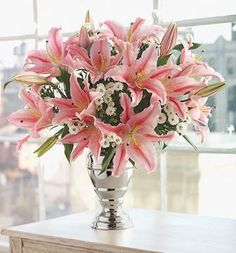 Oriental pink lily with small white flowers arrangement with elegant silver vase