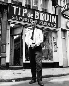 Kledingverkoper Tip de Bruin voor zijn winkel op de Nieuwendijk Amsterdam 1965.
