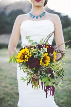 Modern and bohemian sunflower, plum, and feather bridal bouquet
