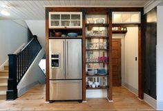 Open shelves with structural strapping add storage and display options  Custom divided lite window sash above the fridge and behind the shelving separate the pantry space from the display area  inspired by the feeling of small town grocery shop storefronts  Photos by Photo Art Portraits #kitchendesign