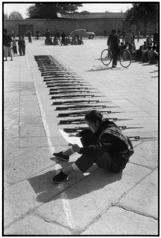 """© Henri Cartier-Bresson/Magnum Photos CHINA. The """"Great Leap Forward"""". Beijing. 1958. At ease beside the arms of her unit, a woman member  of the People's Militia catches up on official reading matter before beginnning her daily drill."""