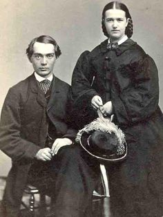 Finely dressed couple. Husband wears dark suit, overcoat, tie. Wife wears paletot, bowtie, hat with ostrich plume. Both wear rings. Wedding picture?