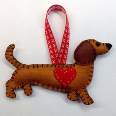 Handmade Dachshund Ornament. Ideal Valentines Gift! These are drawn and completely hand sewn by me using felt, thread, polyester stuffing, a little bead for the pooches eye and a ribbon loop for hanging. Dogs can be made to order and personalised/customised with different ribbon/string, messages or a name stitched in the back. Please send me a message if you have any special requests. Items will be sent within the UK via first class post and by airmail to locations overseas