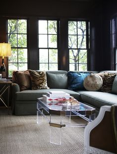Dark, high gloss walls, mismatched pillows, lucite and brass table.