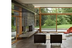 Asymmetrical stone fireplace passes through exterior wall with matching bench/hearth on outside.