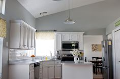 Sherwin Williams Argos gray walls, cabinets painted white, subway tile.
