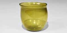 """6th century AD. A bulbous green cup with flattened base and everted rim; probably Gaulish, curated in a Kentish grave. Cf. the 4th century AD Roman green glass cup in Ancient Glass, Roman Glass (Allaire Collection of Glass) from Bourne Park, Bishopsbourne, Kent and Evison, V.I. Catalogue of Anglo-Saxon Glass in the British Museum, item 97. 89 grams, 78 mm (3"""")."""