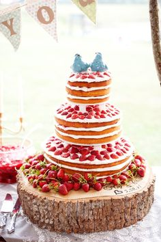 a spectacular strawberry tower wedding cake, topped with two blue birds