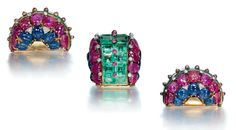 A SET OF RETRO MULTI-GEM JEWELLERY  Comprising a brooch of bombé design, the front set with graduated square-cut beryls, enhanced by a line of cabochon ruby collets, the sides set with lines of carved rubies and sapphires, to the diamond detail, a pair of ear clips en suite, mounted in gold, circa 1940