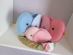 Que linda família de passarinhos no ninho para enfeitar o quartinho do seu bebê! <br> <br>Confeccionada em feltro, com asinhas de tecido e detalhe de botãozinho! A família foi colocada no ninho de sisal. <br> <br>Pode ser feito em outras cores, a sua escolha.