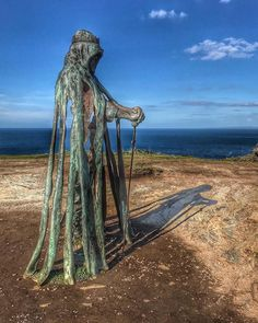 tanding on top of the cliffs high above the sea and looking towards the ruins of Tintagel Castle stands the imposing bronze figure of King Arthur (cornwall) Time Relativity, Tintagel Cornwall, King Arthur, Black Queen, Great Britain, Places To See, Castle, Sculpture, Statue