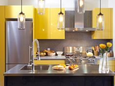This glossy, intense yellow is the perfect color stands up to August's scorching sun and is just as appropriate as cooler fall temperatures hit. This happy color steals the spotlight in this contemporary kitchen design by HGTV's Kitchen Cousins. Yellow Kitchen Cabinets, Stainless Steel Kitchen Cabinets, Kitchen Cabinet Colors, Painting Kitchen Cabinets, Kitchen Paint, Kitchen Colors, Kitchen Countertops, New Kitchen, Stainless Countertops