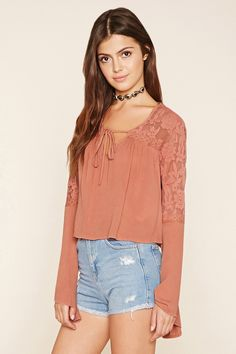 A woven gauze top with a self-tie split neckline and floral lace panels along the yoke and the long bell-sleeves.