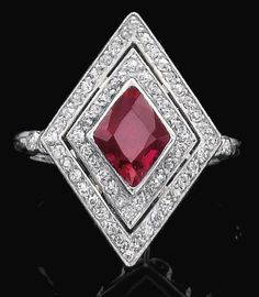 Ruby and diamond ring. Collet-set with a lozenge shaped ruby framed by two rows of circular-cut diamonds, the shoulders similarly set, size 53, numbered, French assay marks. Sotheby's.