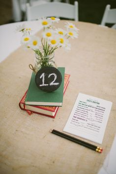 simple daisy centerpiece on top of books with chalkboard table numbers  http://www.weddingchicks.com/2013/10/17/simple-sweet-wedding/