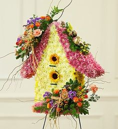 A beautiful bird house floral arrangement.