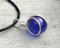 These are lovely 14mm (1/2) in diameter round cobalt blue glass marbles that we cleverly wire wrapped with 18 gauge sterling silver wire. The entire pendant measures just about 1 1/8 (2.8cm) from the very top of the bail to the bottom of the pendant. This pendant comes with a