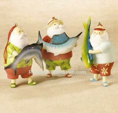 Deep Sea Fishing Santas--3 Fabulous fishing Santas - Each Santa ornament uniquely different in color and style, yet following with the sportsfishing theme. One Santa holds a Dorado, or Mahi mahi, another a sailfish, and the last a black marlin. If there's an ocean fisherman in your life - this set of ornaments is perfect!