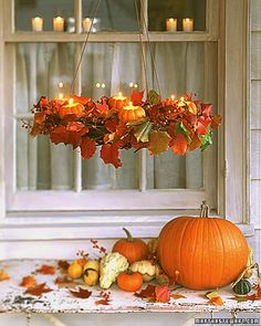 Autumn Wreath Pumpkin Chandelier    Casually adorned with colorful fallen leaves, a simple grapevine wreath is illuminated by tea lights set inside mini-pumpkin holders. Suspended from a ceiling hook, it gives a warm, rustic atmosphere to a front porch. To make the glow last, light the candles just before your guests arrive.