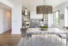 Eating in style: Flowing into the kitchen, a large stone table governs the middle, lit up by a statement lamp