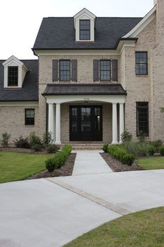 Amazing front door area. Walnut-colored operable composite raised-panel shutters look beautiful with this home's dark brown windows and washed and aged tumbled-brick exterior.