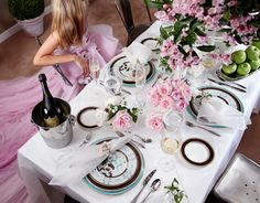 Tablesetting with blue and brown plates, pink roses, and champagne in silver bucket.