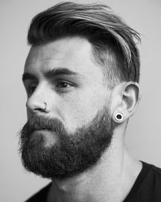 Nathan McCallum with a full beard, nose piercing, and undercut style.